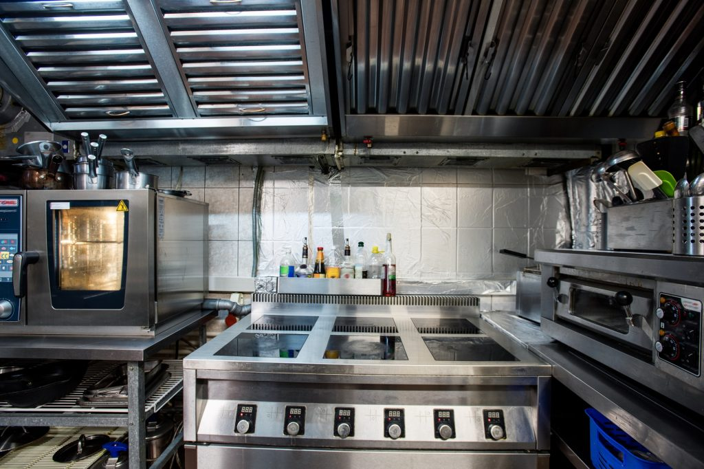 Part of interior of modern restaurant kitchen including electric stove and oven